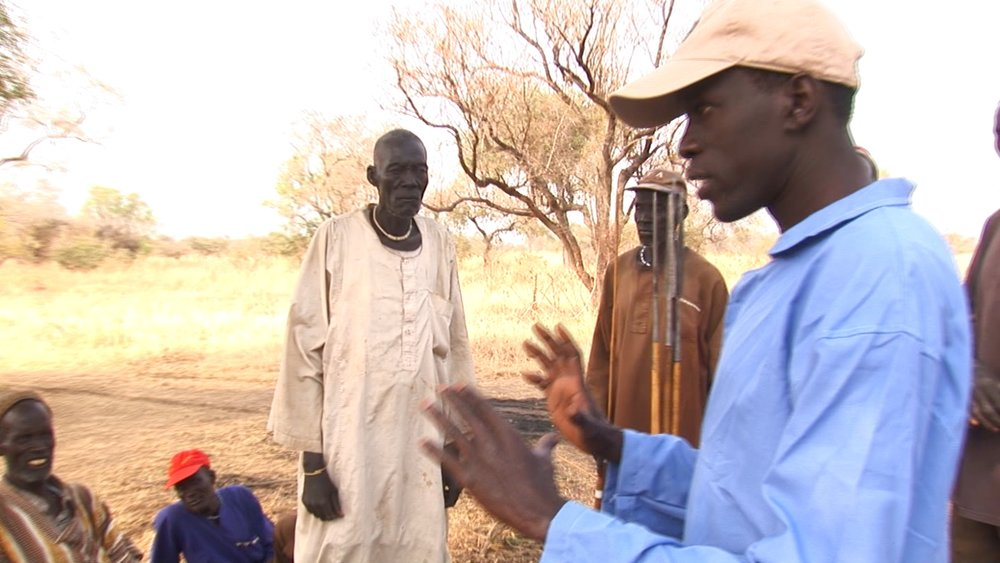 Salva describing the well drilling process to villagers