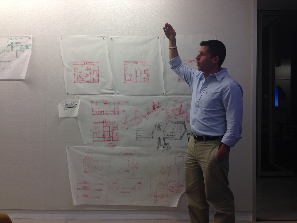 Chris Bonarrigo explaining his team's vision of how to utilize the movable tools in micro housing design for a family of four.