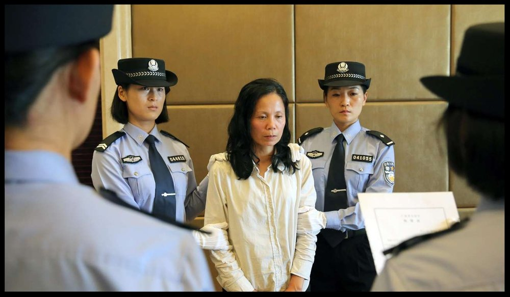 Kuang Wan Fang is processed by police at Changle Airport in Fuzhou, on September 24, 2015, after arriving on a forced repatriation flight.  Photo: Xinhua