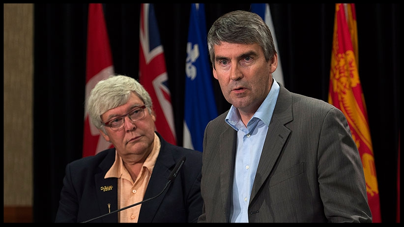 Nova Scotia Premier Stephen McNeil talks with reporters at the annual Council of the Federation meeting in Charlottetown in 2014 as then Alberta premier Dave Hancock looks on . (Andrew Vaughan/The Canadian Press)