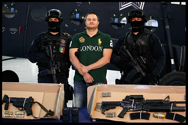 Federal police stand guard by Texas-born fugitive Edgar Valdez Villarreal, alias 'the Barbie,' center, as he is presented to the press along with weapons allegedly seized during his arrest in Mexico City, Tuesday Aug. 31.