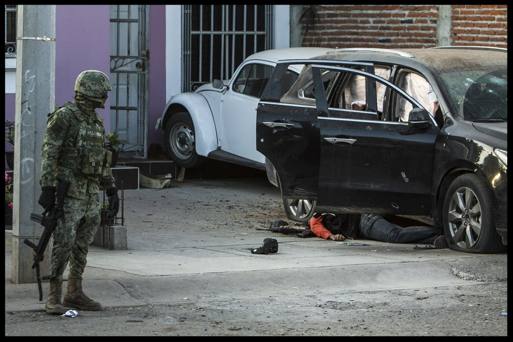 A Mexican marine looks at the body of a gunman next to a vehicle after a gun fight in Culiacan, Mexico, February 7, 2017.(AP Photo/Rashide Frias)