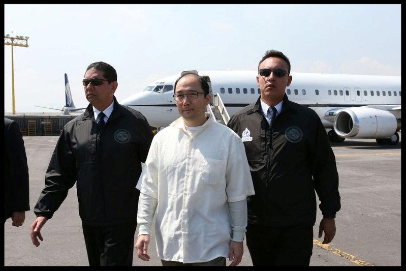 Zhenli Ye Gon, a businessman accused of working with drug cartels, is escorted by Interpol agents after arriving from the United States on a extradition flight in a hangar belonging to the office of the Attorney General in Mexico City, Mexico, October 18, 2016. REUTERS/PGR - Attorney General's Office/Handout via Reuters