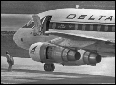 July 1972 file photo of an FBI agent wearing only swim trunks, as per the hijacker's instructions, carrying a $1m ransom to the Delta DC8 plane in Miami. George Wright is wanted in connection with the hijacking.