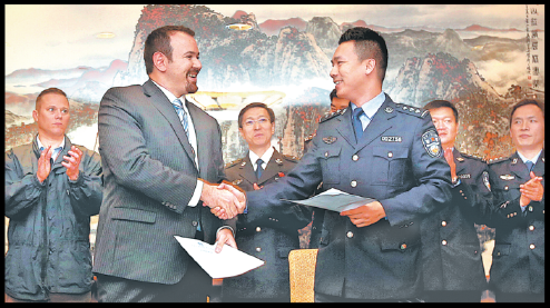 A representative of the International Cooperation Department of the Ministry of Public Security (right) hands the memorandum of understanding to a representative of the United States Department of Justice in Shanghai on Oct 16. CHINA DAILY