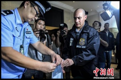 A Chinese police officer hands over a U.S. fugitive's personal belongs to the U.S. police. (File photo/China News Service)