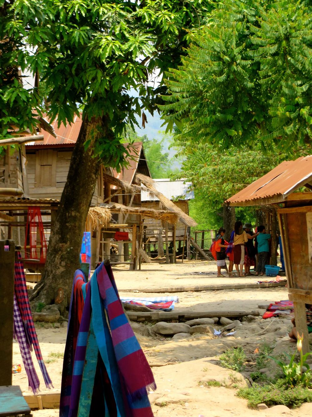 """Hill Tribe village. Here, many people are weavers, so they sell scarves. What they don't sell goes into """"town""""which is Luang Prabang, where I'm headed."""