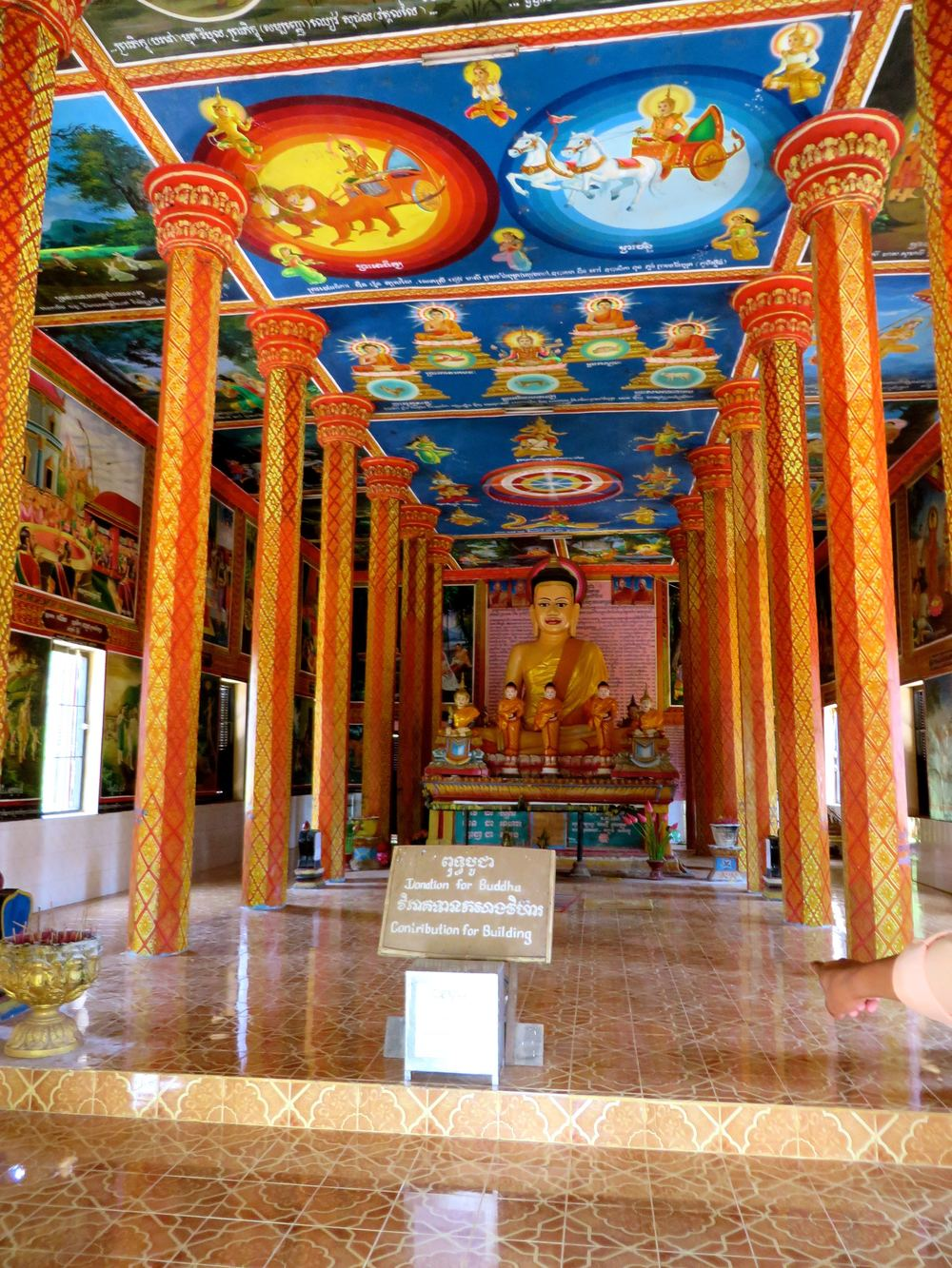 Buddhist temple in Siem Reap.  Painted + bright, telling the story of Buddha, clearly different than previous temples seen in Laos and Thailand.  A lot of the temples are new as they were built post 1980.  The Khmer Rouge forced monks to take off their robes and work in the fields as well, to illustrate equality among men.
