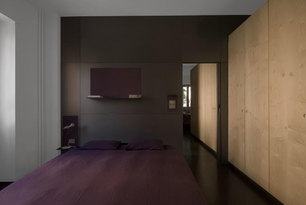 La camera da letto principale, con la parete in metallo a fare da testata del letto e il blocco degli armadi in legno sulla destra
