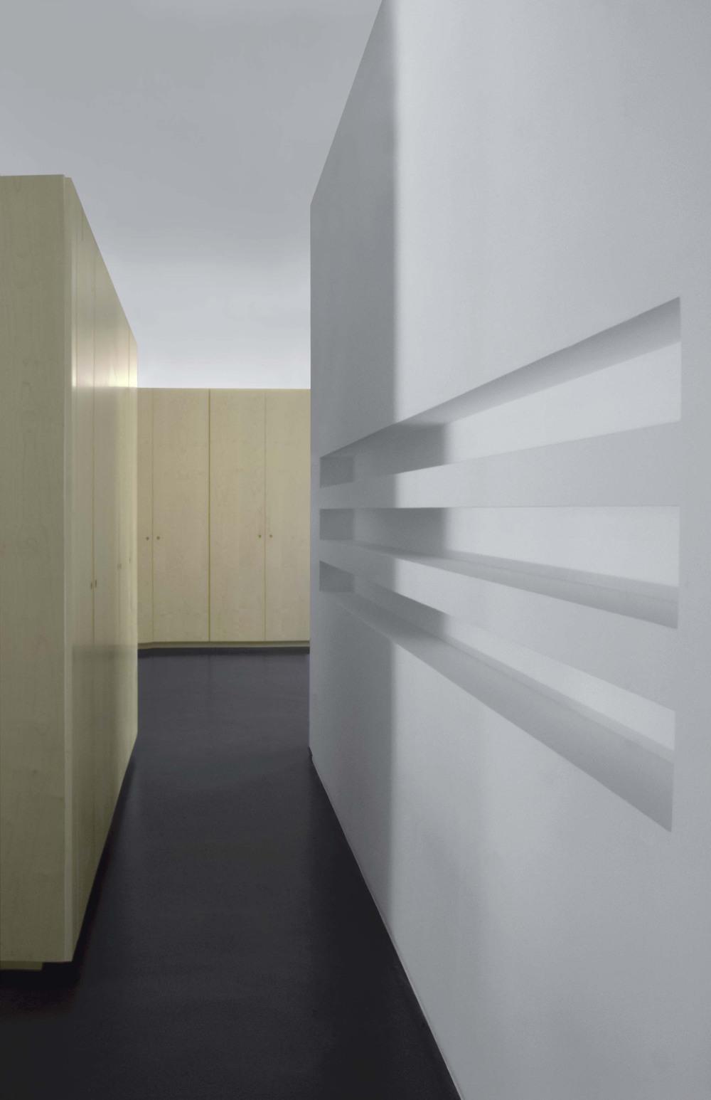 L'ingresso, con i bliocchi di arredo in legno che organizzano la casa e tre grandi nicchie per i CD ricavate nella parete.