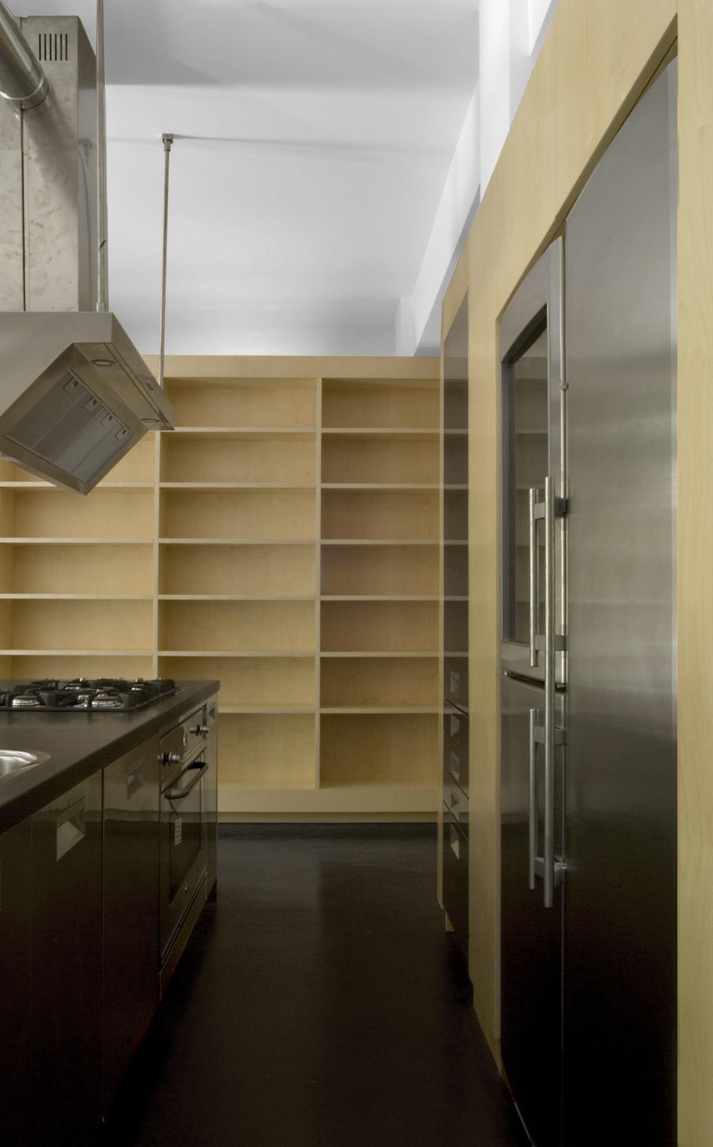 Il centro della casa, la cucina, con lo sfondo della libreria che la separa dalla zona notte.