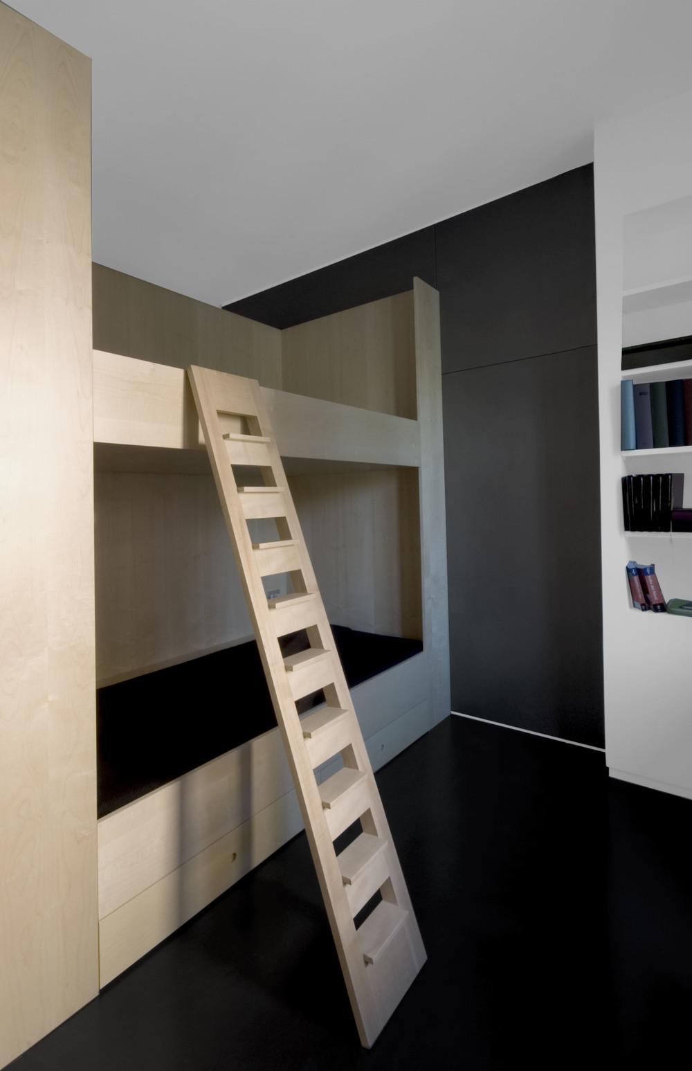 La camera da letto per i bambini, con il blocco dei letti e la libreria sulla destra.