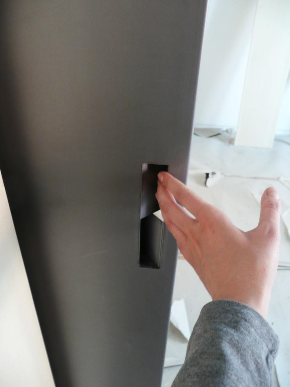 La maniglia della porta in metallo, realizzata con la lamiera di ferro piegata.