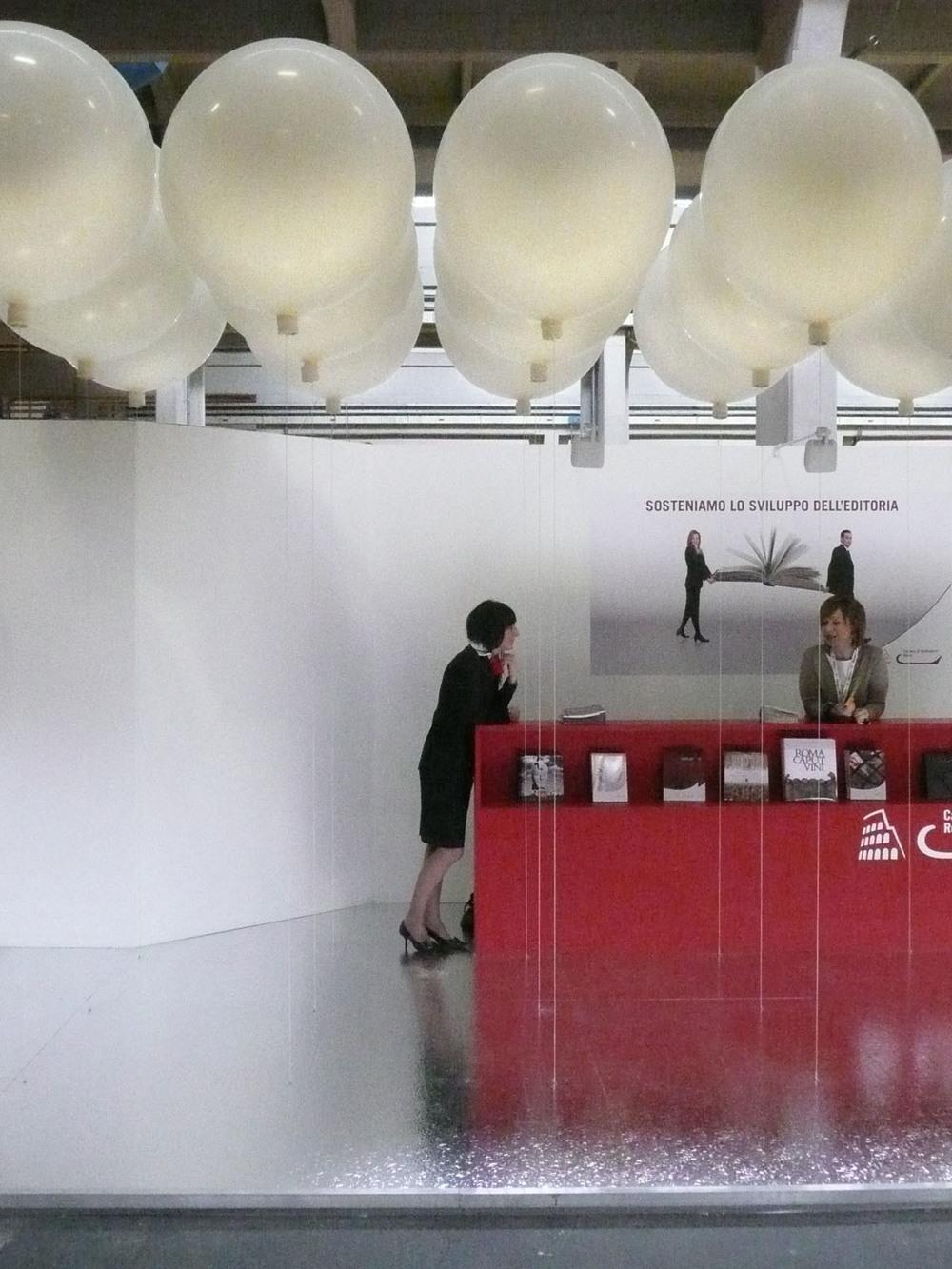 Vista frontale dell'allestimento, con il desk espositivo che si riflette sulla pavimentazione e il cielo di palloni sospesi.