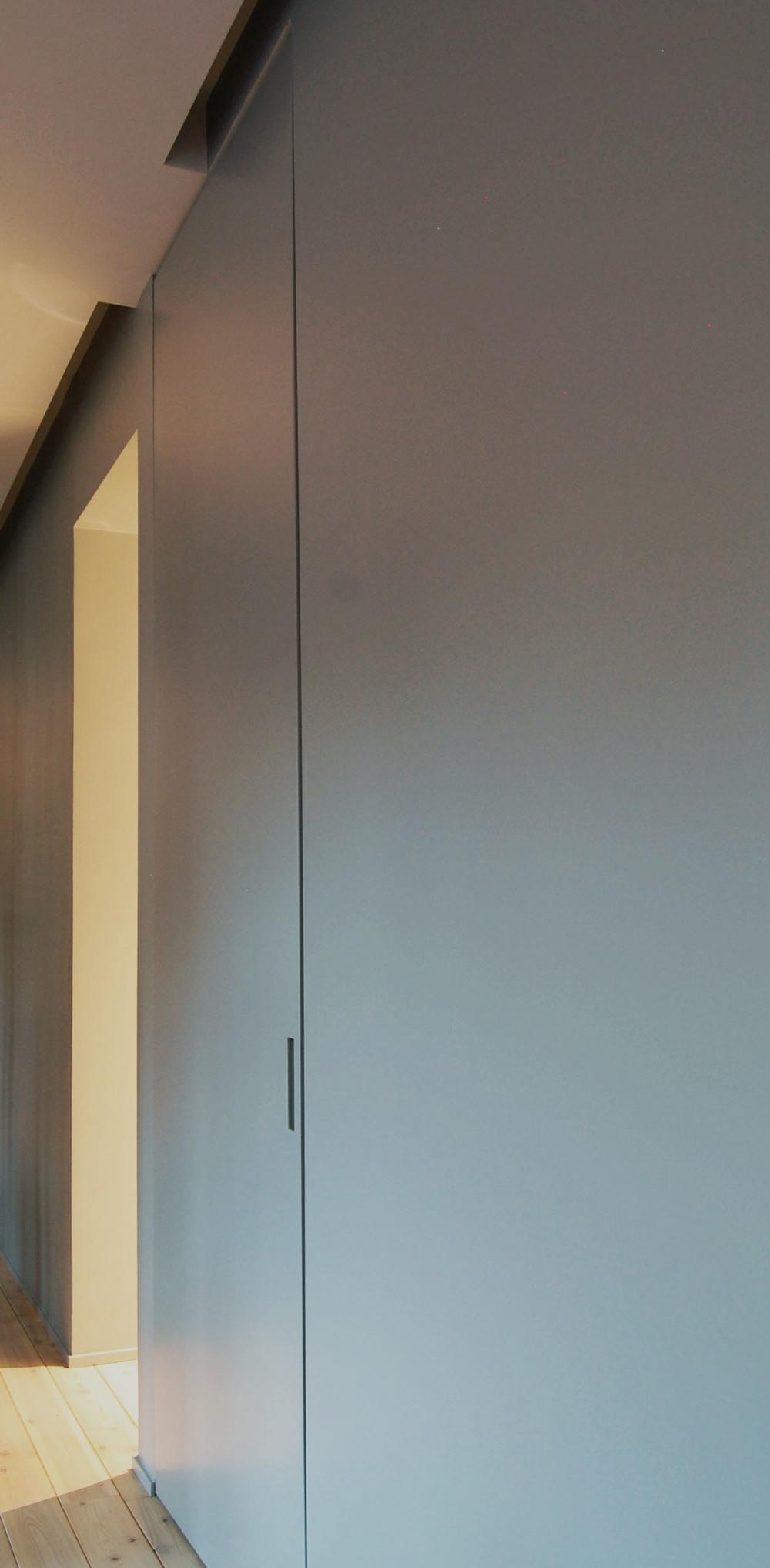 Il muro attrezzato in un'immagine di scorcio: si nota la porta a scomparsa che chiude il passaggio versa la zona notte e il varco che porta alla cabina armadio.