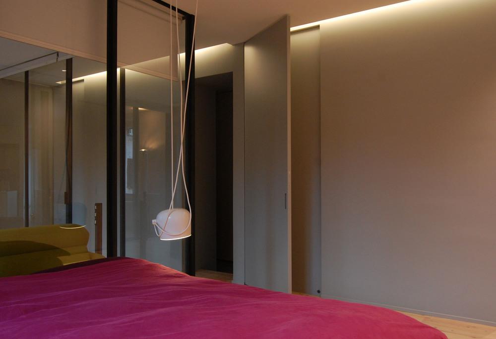 La zona notte, con la porta a scomparsa che garantisce la necessaria privacy e la parete della stanza vetrata alle spalle del letto.