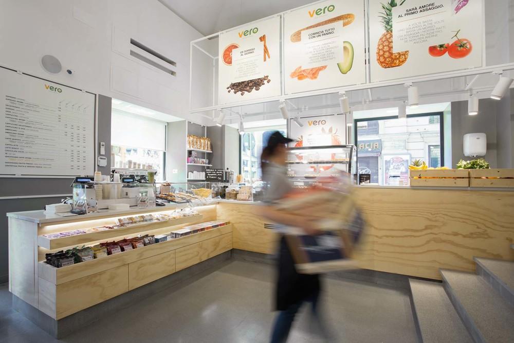 La zona del bancone del nuovo punto vendita con il grande elemento scenico del traliccio metallico, supporto per la comunicazione e l'illuminazione.