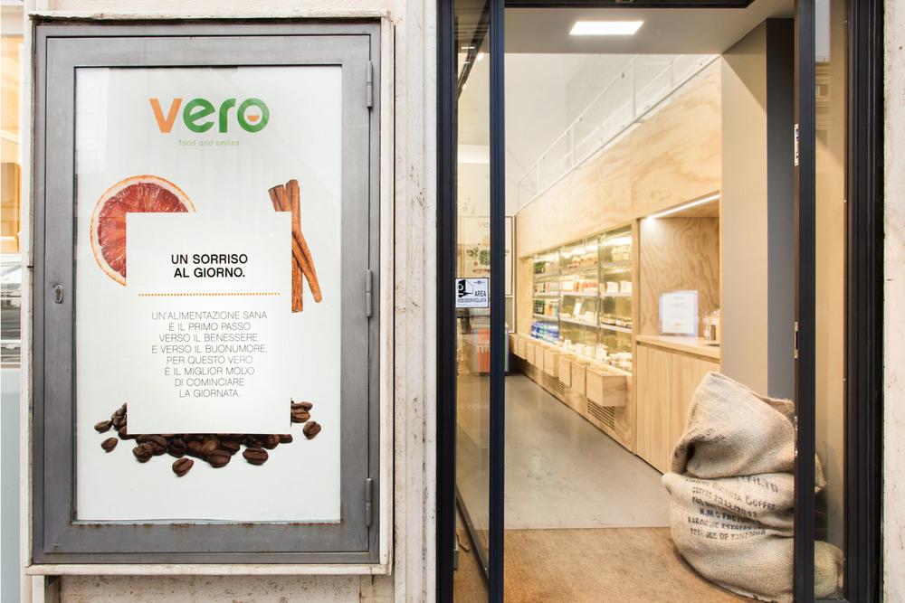 L'ingresso in una fotografia dall'esterno, con la grande parete frigoriferi sulla destra.