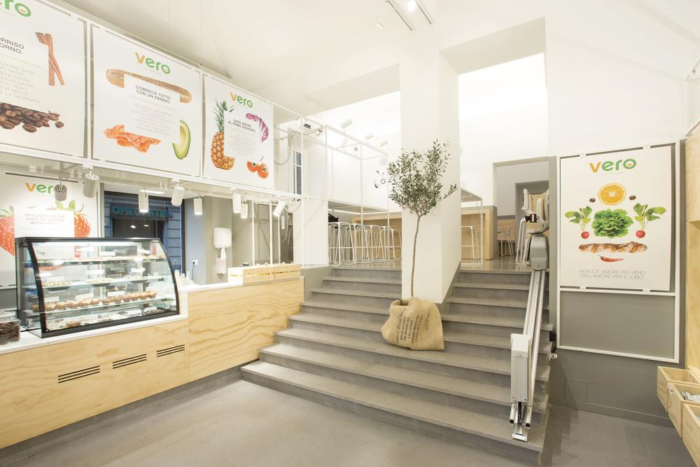 L'ingresso del nuovo punto vendita, con il bancone sulla sinistra e la grande scala che collega i due livelli. A unire visivamente gli ambienti contribuisce il traliccio metalicco, che da elemento tecnollogico diventa banco per la consumazione veloce.