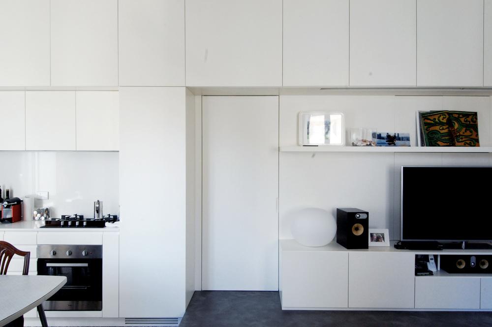 La parete attrezzata, con la cucina sulla sinistra, la zona tv/stereo sulla destra e la porta di accesso alla zona notte inglobata nel sistema.