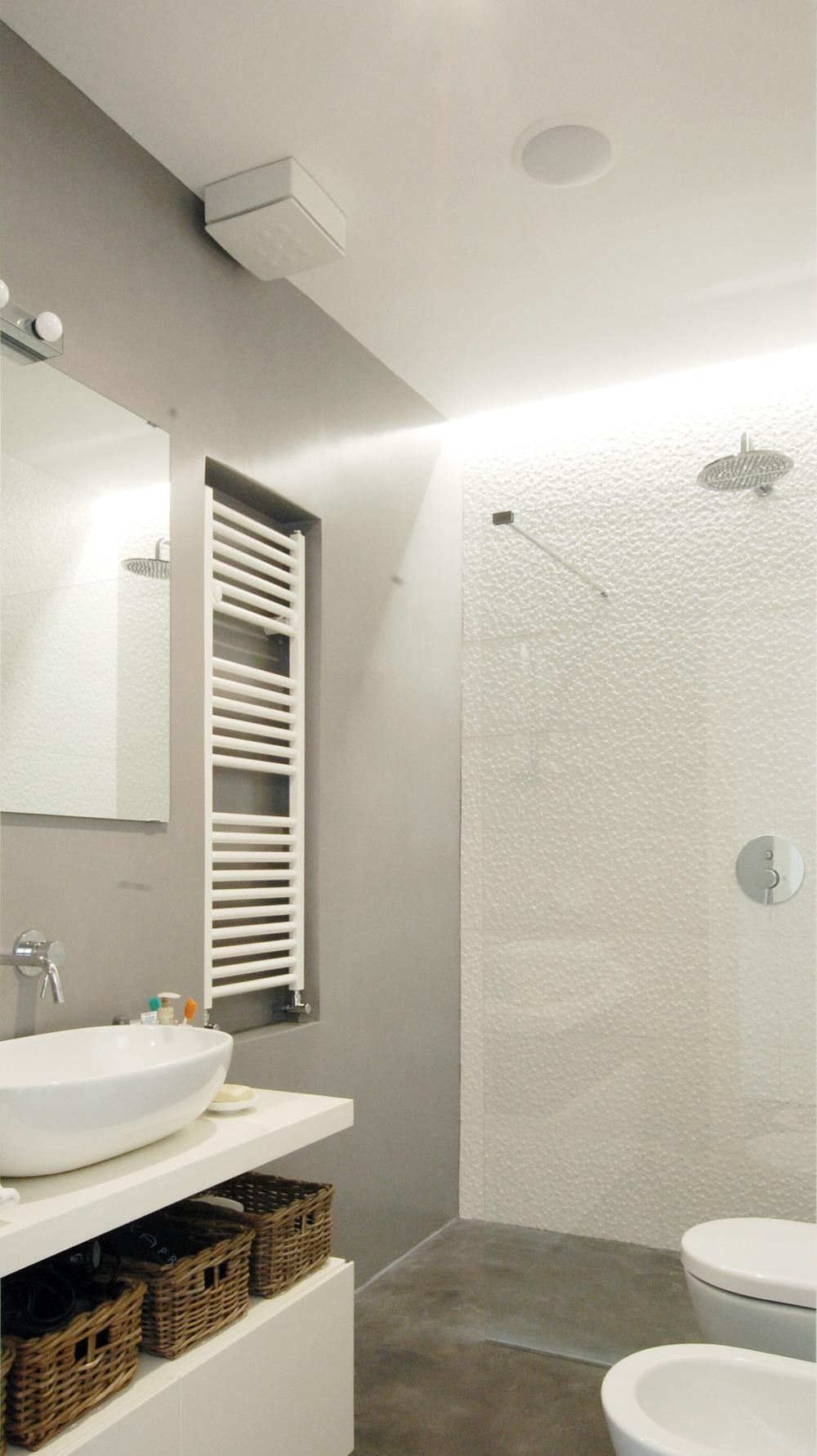 Il bagno, con la doccia a filo pavimento e la luce radente la parete.