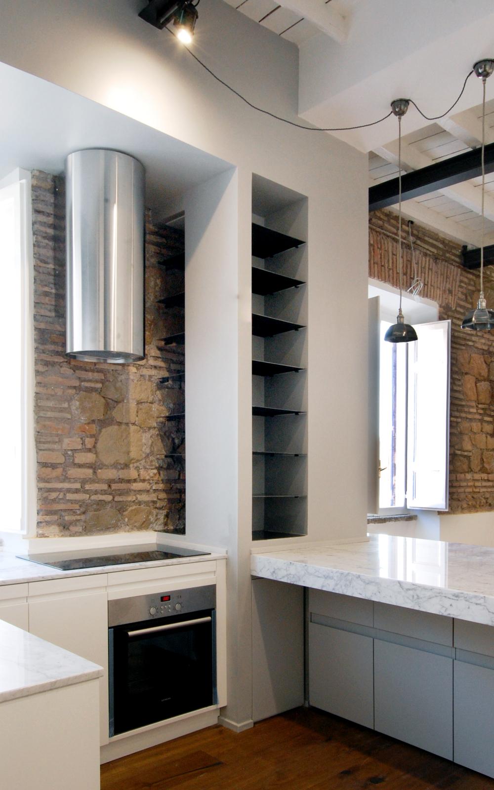 La cucina aperta sul living, con la zona cottura contenuta nello spessore del setto di servizio grigio e riparata alla vista dal piano in marmo.