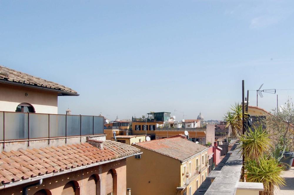 La terrazza, con la vista sui tetti di Trastevere e i colori della città.