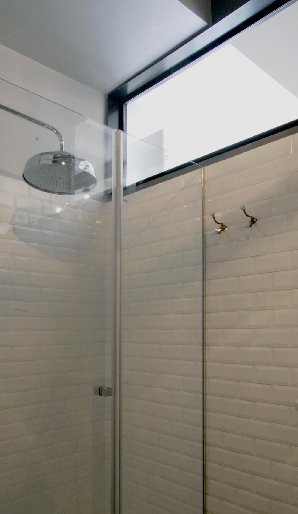 Uno scorcio della doccia, con il telaio della superficie vetrata che ribatte lo spessore del muro divisorio.