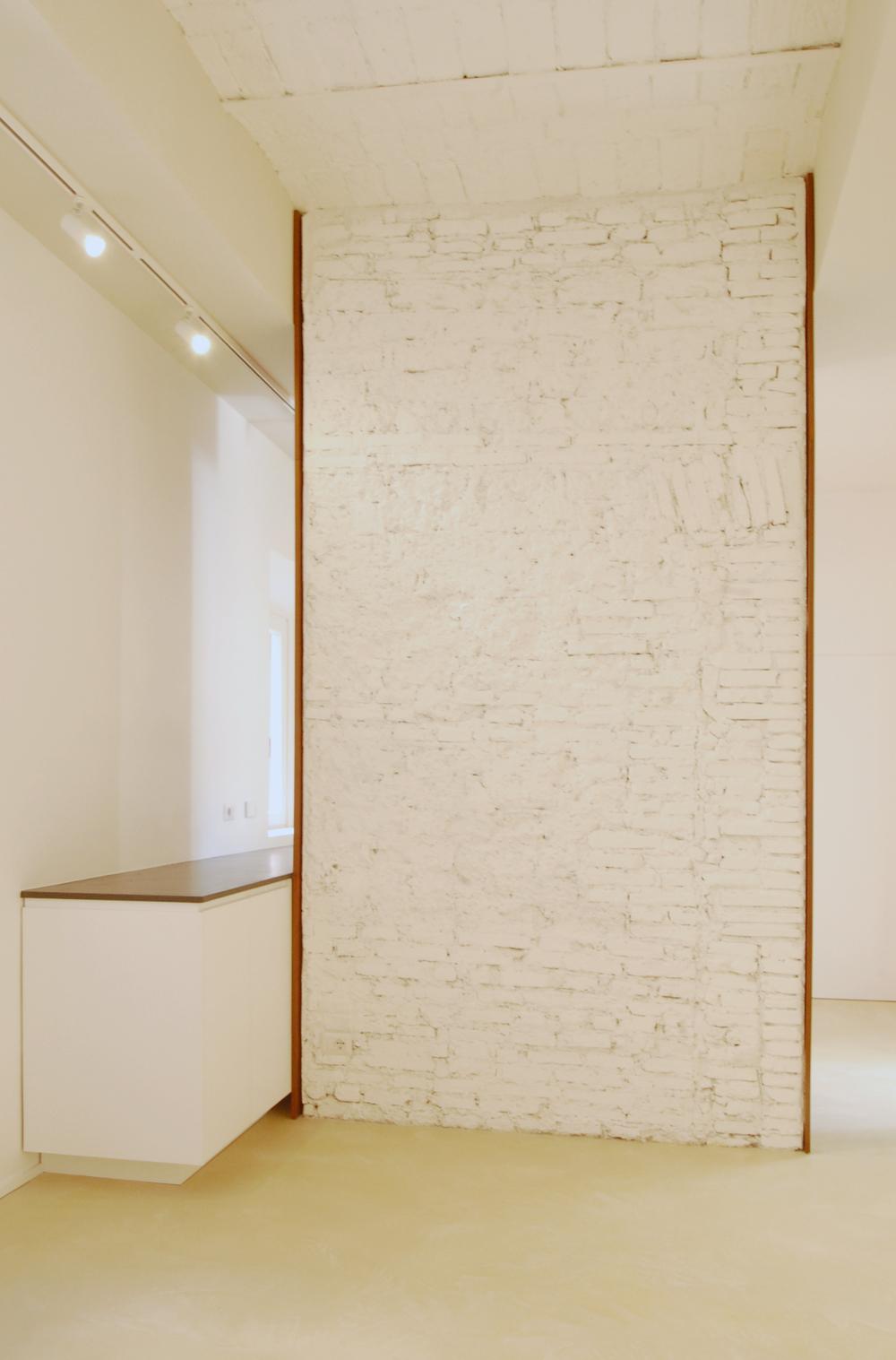 La visuale di entrata, con il setto in muratura a vista in primo piano a dividere la zona living dalla cucina. La sua larghezza misura anche la porzione di soffitto a voltine riportato alla luce.