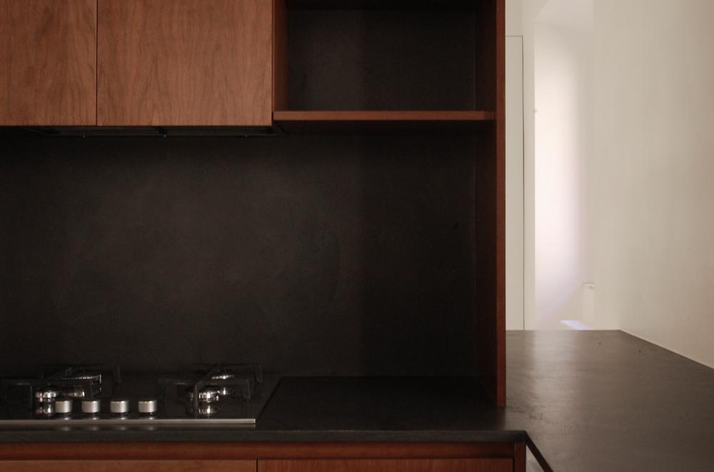 Immagine di dettaglio: la parete attrezzata della cucina in primo piano, con la luce proveniente dalla zona living sullo sfondo.