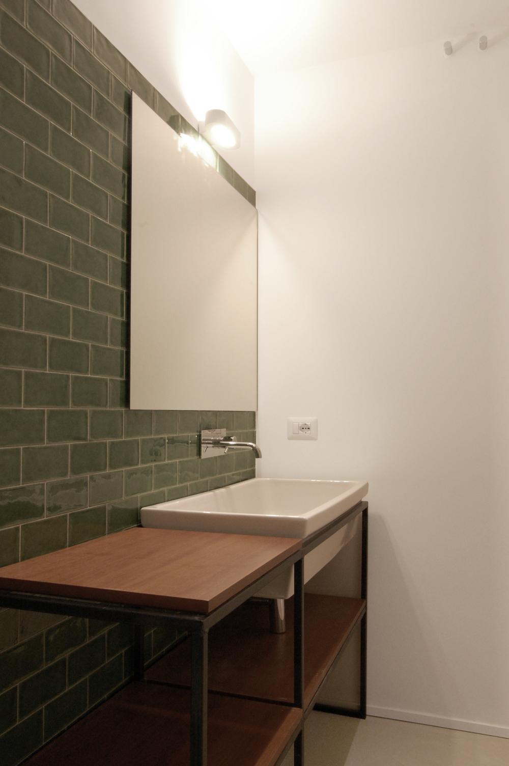 Una sottile struttura metallica accoglie il lavabo e organizza gli spazi del bagno.