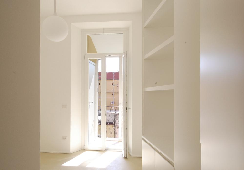 La camera da letto in uno scorcio d'entrata, con il balcone sullo sfodo.