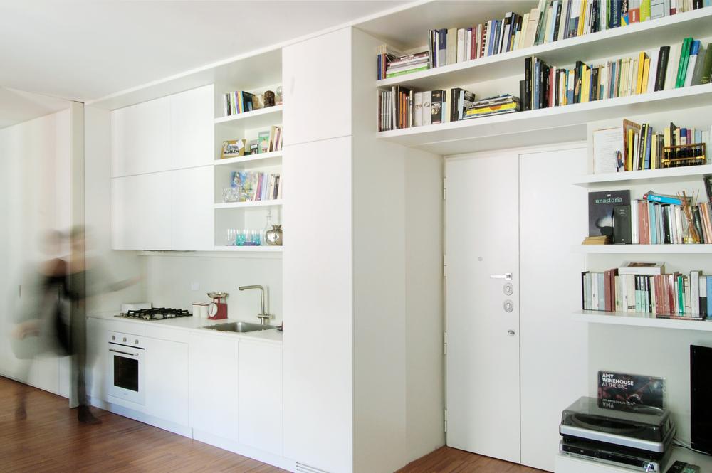 La parete attrezzata con la cucina in primo piano: i libri invadono lo spazio normalmente dedicato alla cottura, rendendo chiara la fusione delle funzioni e razionalizzando gli spazi a disposizione.