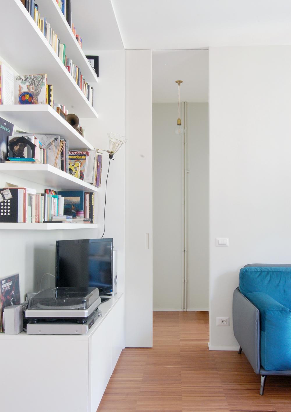 Dal living al disimpegno che dà accesso al bagno, con la libreria sulla sinistra e la porta scorrevole a tutta altezza in primo piano,