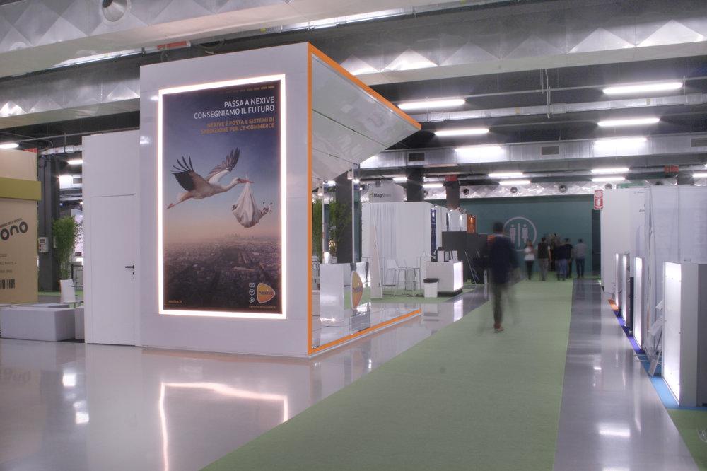 La parete dello stand con la grande immagine pubblicitaria incorniciata da luci led.
