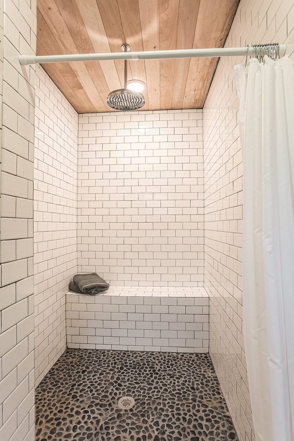 Subway tiled main house master bath with relaxing rain shower and river stones that massage your feet.