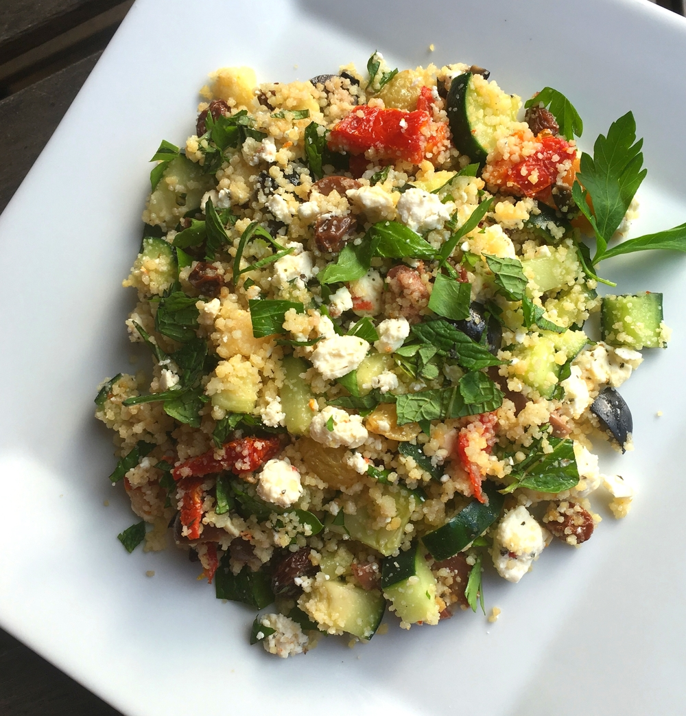 Couscous salad with fresh herbs, sun-dried tomatoes, black olives, cucumber, lemon, feta