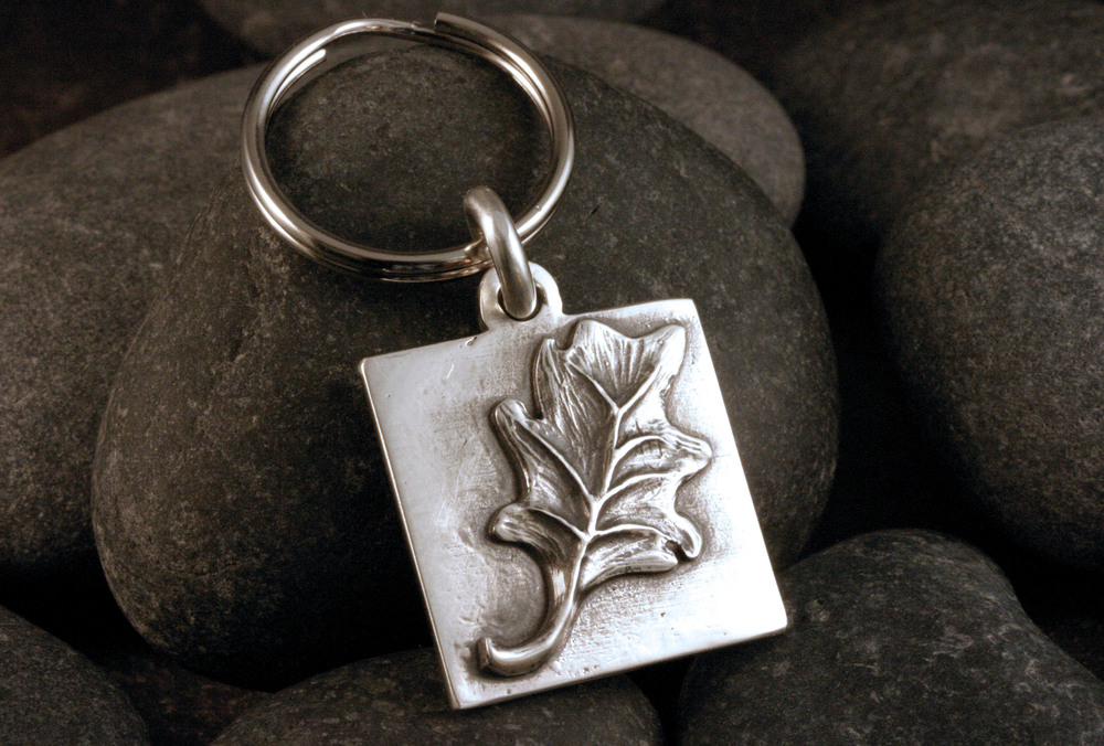 A hand carved sterling silver leaf keychain.
