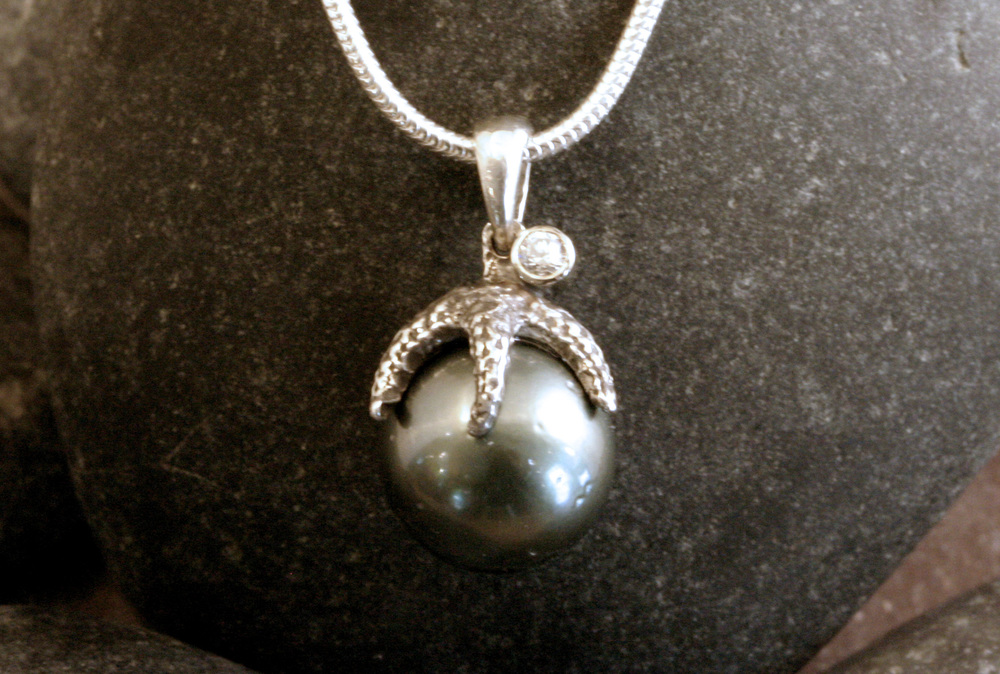 A sterling silver Tahitian pearl, diamond, & starfish pendant.