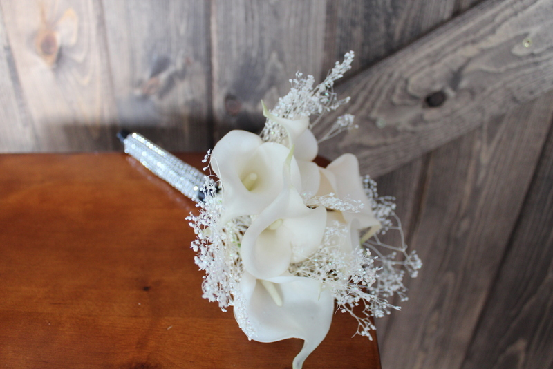 Toss Bouquet of white Calla Lilies and preserved Baby's Breath with rhinestone wrap on the stems.