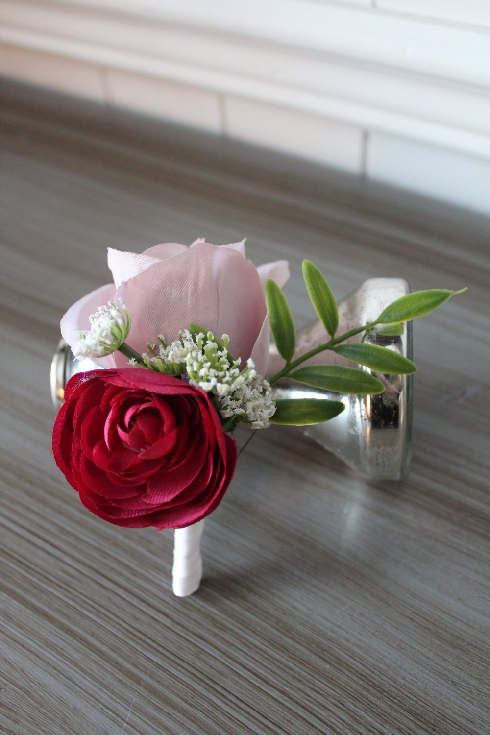 A mauve Rose, burgundy Ranunculus, and a touch of Queen Anne's lace and fern make for an awesome groom's boutonniere.