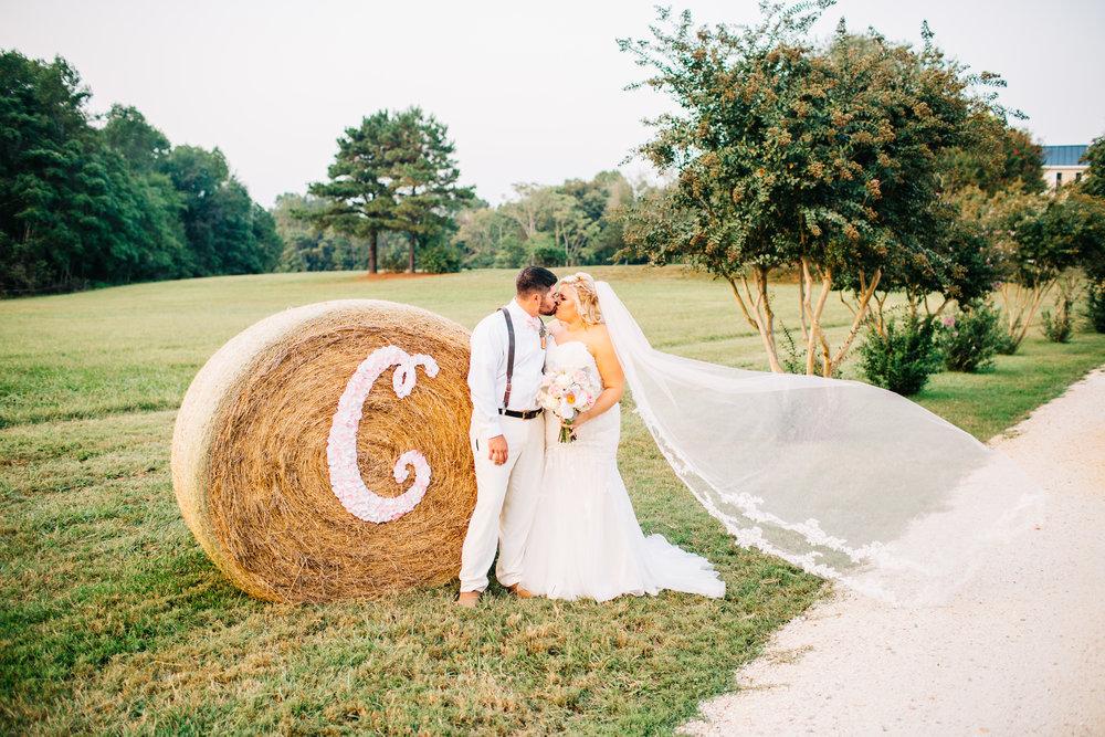Bride and Groom in front of Monogram Hay Bale