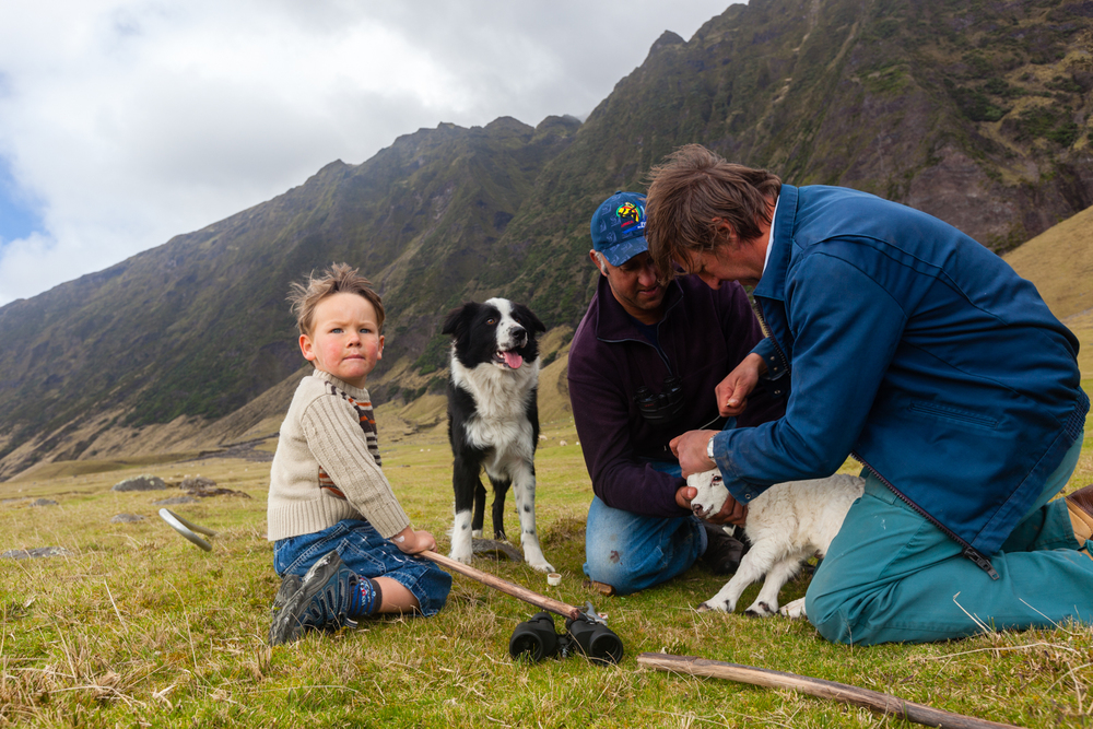 Volcanic slopes loom over locals tending to a lamb. Credit: Andy Isaacson