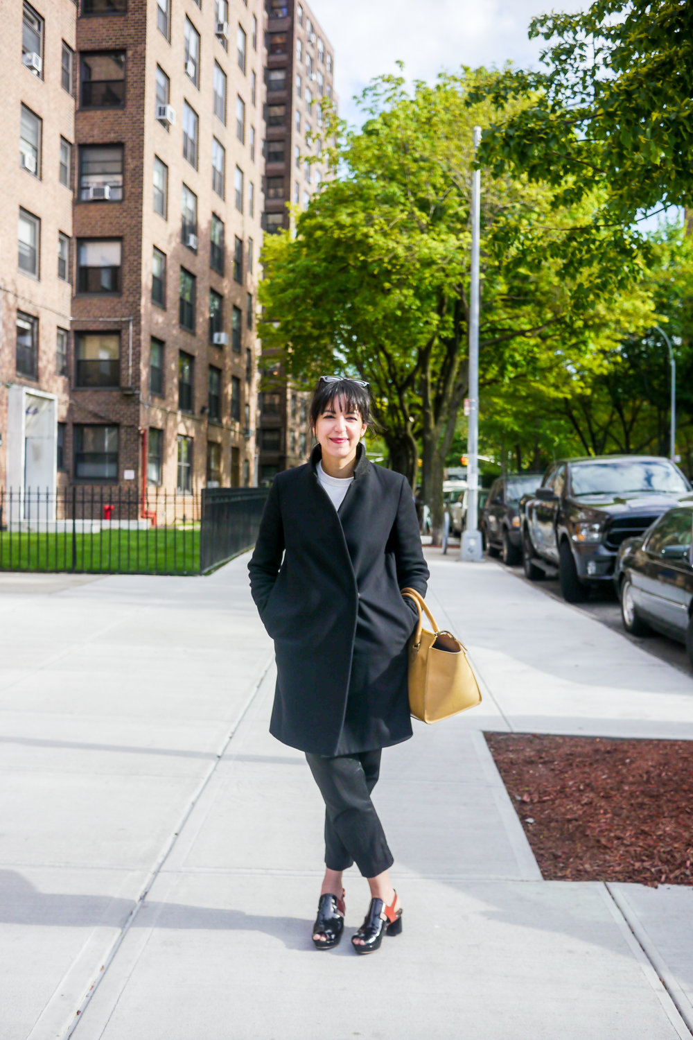 Coat, COS ; Pants, M. Patmos ;  Sweatshirt, Everlane  ;  Shoes, Rachel Comey  ;  Bag, Clare V.