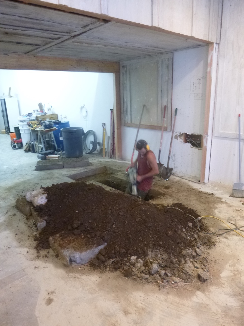 In search of the building's main drain line: Creative director, brewmaster, and owner Nole Cossart digging deep. Note the salvaged wall panels from discarded furniture storage units.