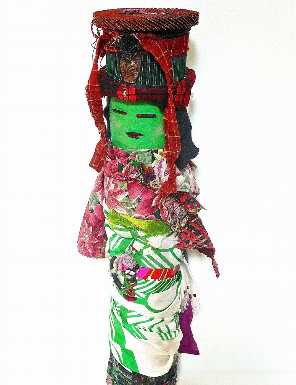 """Green Foreigner   Recycled textiles, rust, sanding disk, paper, yarn, metal, plastic, wood, elastic, glitter, found objects on industrial cardboard tube  22 x 8"""" round  2015"""