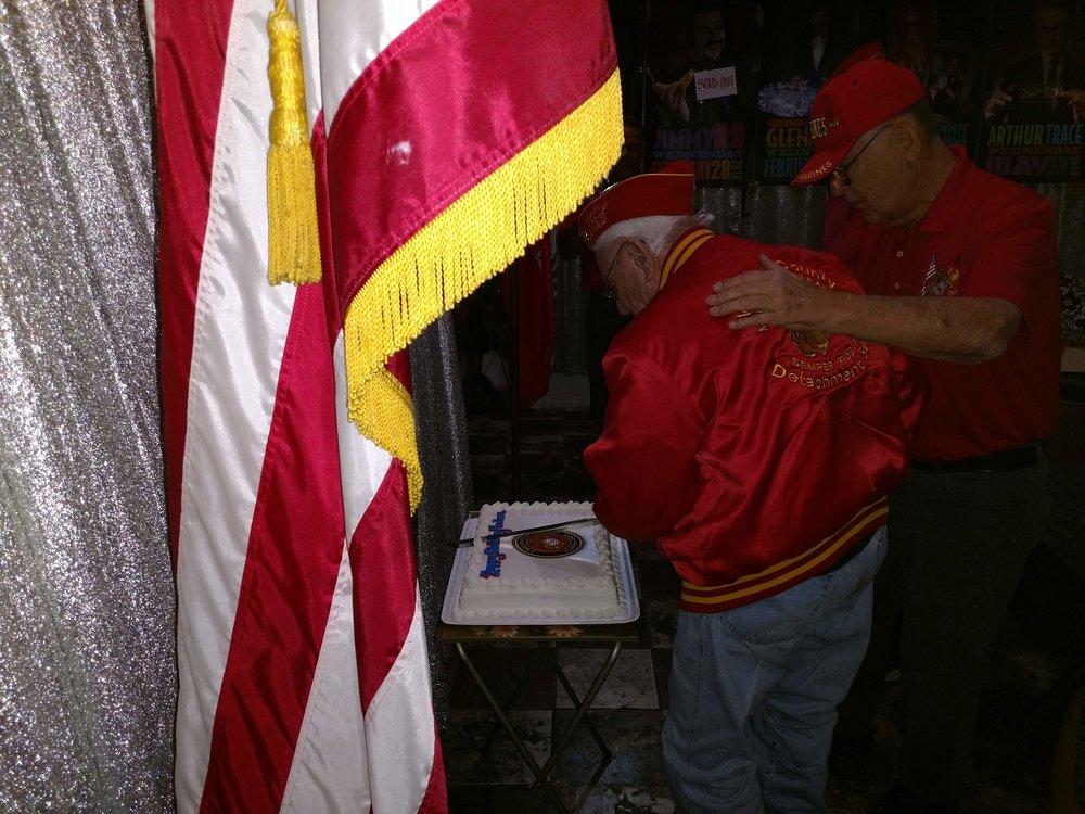 Ben Pfister assisting 86 year old Marine, Bob Obrymski, in cutting the Birthday Cake.