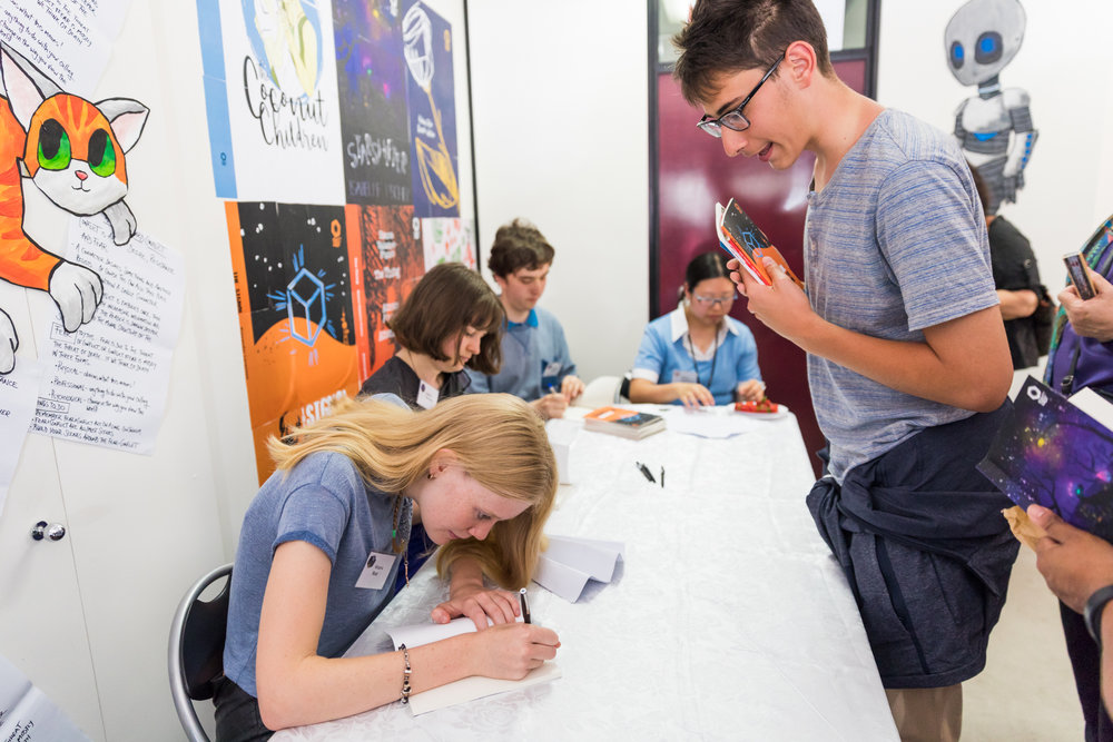 Students sign their work at the launch of of 2017 novellas.