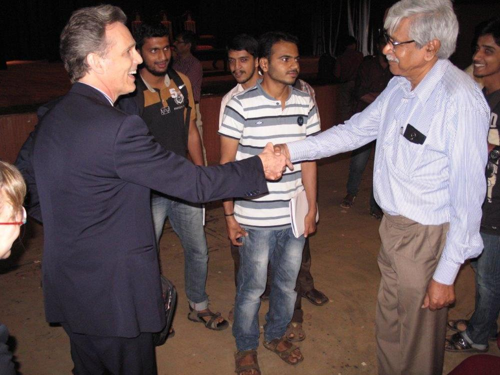 David Wiebers, M.D., shaking hands with physics professor at Mangalore University.