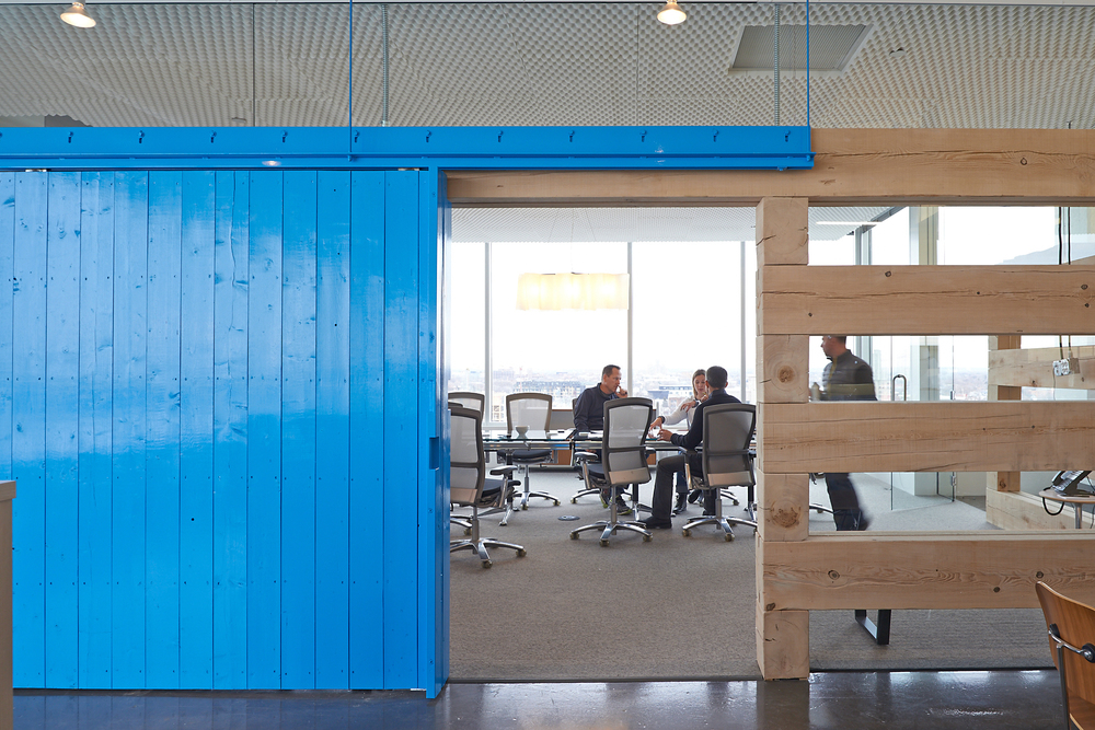Reusable rough-sawn lumber defines a meeting room with salvaged barn doors.